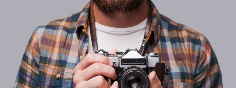 9877090-smile-to-the-camera-close-up-of-young-bearded-man-holding-old-fashioned-camera-while-standing-against-grey-background